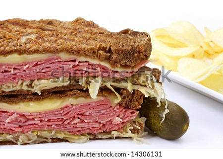 Traditional Reuben sandwich, with grilled rye bread, corned beef, melted Swiss cheese and sauerkraut.  Served with a pickle and potato chips. - stock photo