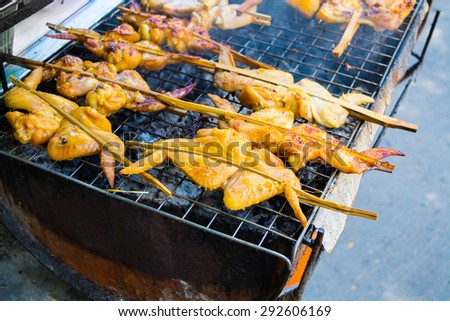 Traditional roasted chicken stick on grill, Thailand - stock photo