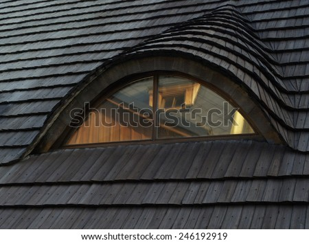 Traditional roof covered with shingles with window in an attic  - stock photo