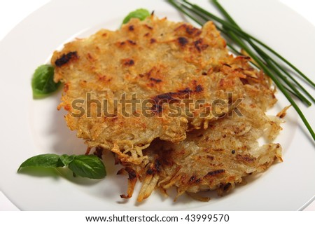 Traditional rosti potatoes in the Swiss style, garnished with chives and basil
