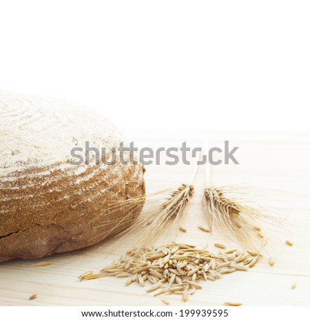Traditional round rye bread lyingon the table and isolated on white background. - stock photo