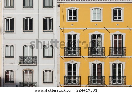 Traditional row houses with white and yellow facades in Lisbon, Portugal. - stock photo