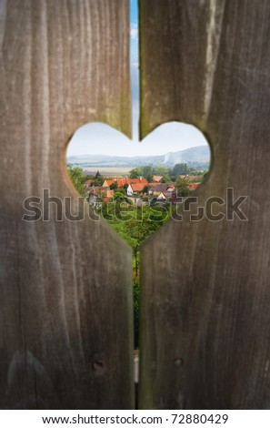 Traditional rural hospitality, looking through a heart shaped window on a wooden door to a landscape with a village. - stock photo