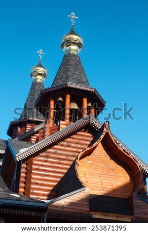 Traditional Russian and Ukrainian wooden orthodox church with lots of bells and gold crosses under the blue sky. The church is located in Kharkov in eastern Ukraine - stock photo