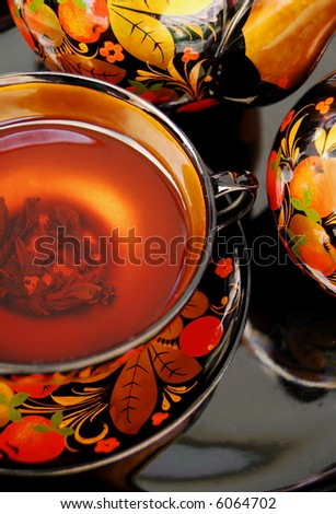 Traditional russian decorated tea service, tea cup with tea. - stock photo
