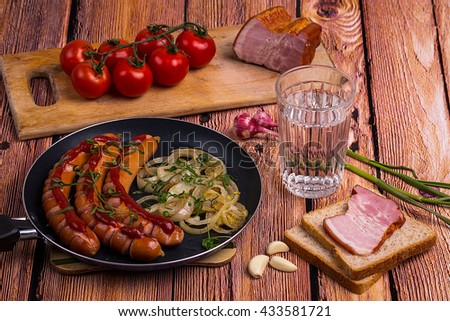 Traditional russian faceted glass of vodka on the old wooden table with snack - fried sausages, pork meat, garlic and chery tomatoes