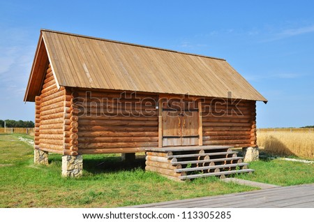 Traditional russian rural wooden house with green grass - stock photo