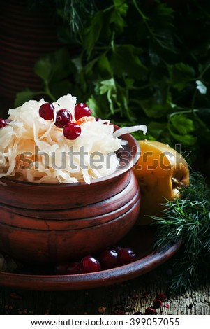 Traditional Russian sauerkraut with pickled apples and cranberries in a clayware, black background, selective focus - stock photo