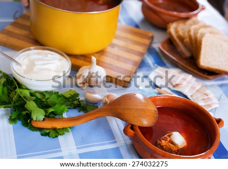 Traditional Russian soup borsch is on the table in a bowl - stock photo