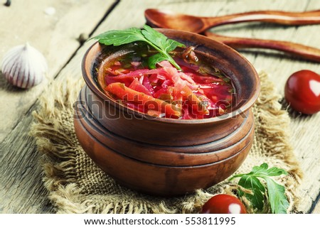 Traditional Russian soup borscht with cabbage, beetroot and tomatoes in a clay pot, vintage wooden background, rustic style, selective focus