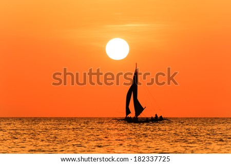 Traditional sailing boat and a tropical sunset on a calm ocean - stock photo