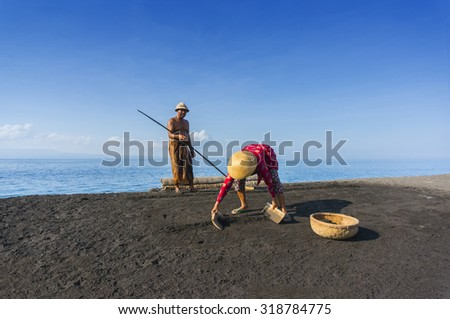Traditional salt farmer at kusambar bali island, indonesia - stock photo