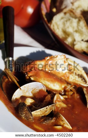 Traditional San Francisco meal of a bowl of cioppino, artichokes and fresh sourdough bread set outdoors on a vintage tablecloth.