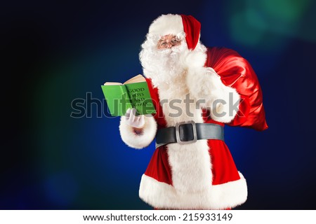 Traditional Santa Claus reading a list of good boys and girls in his notebook. Christmas.  - stock photo