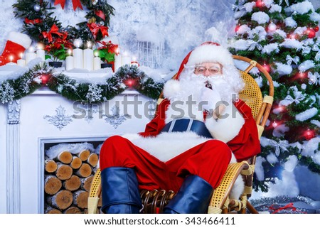 Traditional Santa Claus sitting in a rocking chair in the room by the fireplace and Christmas tree and smokes a pipe.  - stock photo
