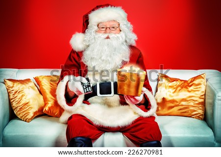 Traditional Santa Claus sitting on the couch watching TV, eating popcorn and drinking soda. Christmas. Red background. - stock photo
