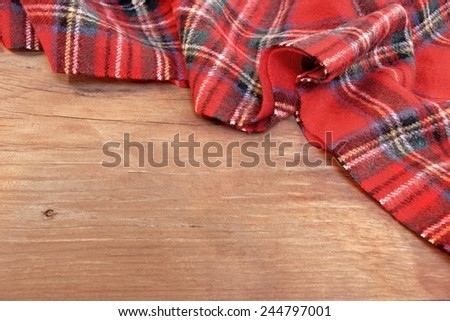 Traditional Scottish Red Tartan  Woolen Soft and Worm Scarf on Grunge Timber Board. Background with Free Space. - stock photo