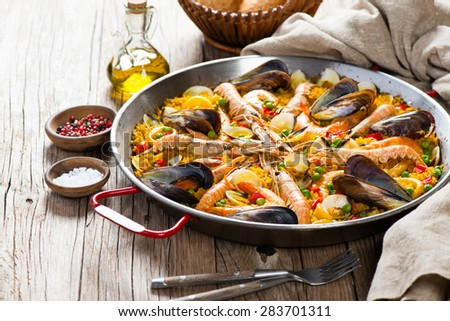 Traditional seafood paella in the fry pan on a wooden old table - stock photo