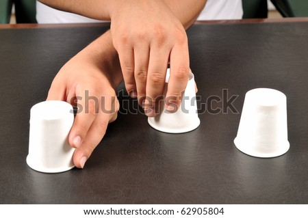 Traditional shell game with three cups - a series of SHELL GAME images. - stock photo