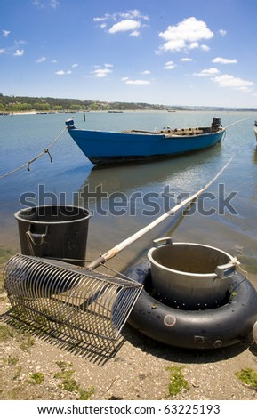 "Traditional shellfish boat ""Bateira"" and typical sand dwelling rake, from the Obidos lagoon at Foz do Arelho, Silver coast, Portugal - stock photo"