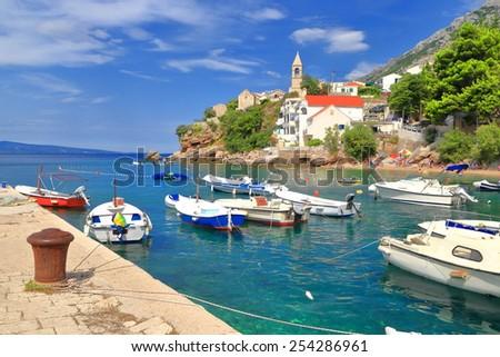 Traditional small harbor with leisure boats and distant church, Dalmatian coast, Croatia - stock photo