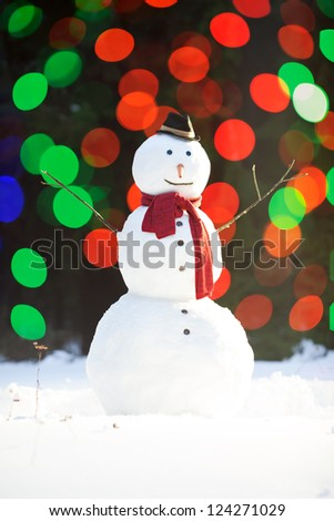 Traditional snowman wearing red scarf and black hat with carrot nose, colorful lights blurred on background - stock photo
