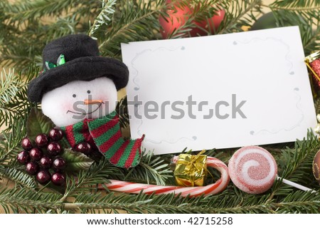 traditional snowman with blank christmas card on fir branch - stock photo