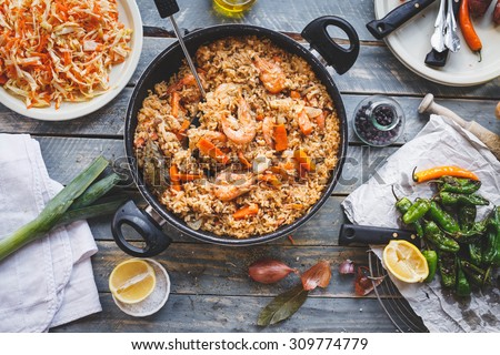 Traditional spanish real food. Homemade prepared paella with chicken meat and seafood produce in pan from above on wooden table with different bbq veggies. Rustic style. - stock photo