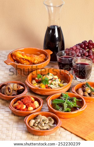 Traditional spanish tapas in terracotta bowls.