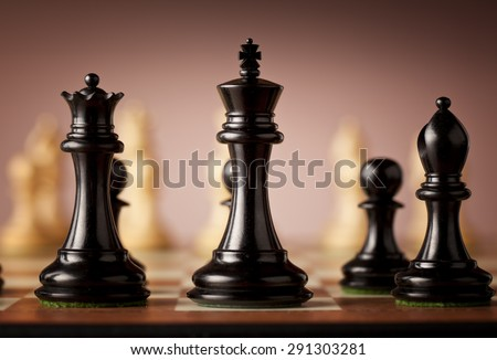 Traditional Staunton black chess pieces carved in genuine ebony in focus standing on   elm burl and bird's eye maple superior chessboard before the game - stock photo