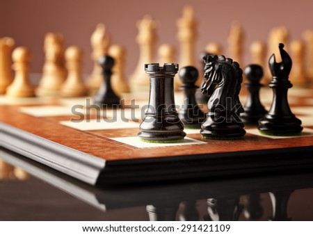 Traditional Staunton chess pieces (black rook in focus) carved in genuine ebony standing on the elm burl and bird's eye maple superior chessboard and glossy table - stock photo