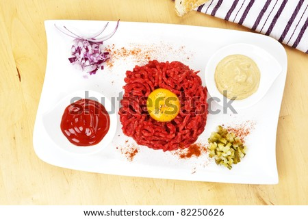 Traditional steak tartare with yolk on white plate. Culinary eating. - stock photo