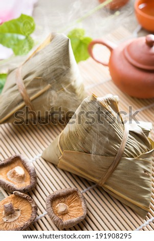 Traditional steamed sticky glutinous rice dumplings. Hot rice dumpling or zongzi. Chinese festive food. Asian cuisine. - stock photo
