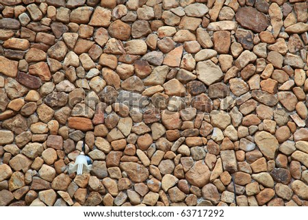 Traditional Stone Brick Wall made of fragment stones in irregular shapes with lamppost