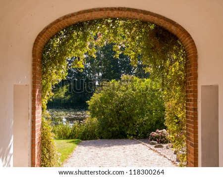 Traditional stone built arch gate leading into a beautiful English garden