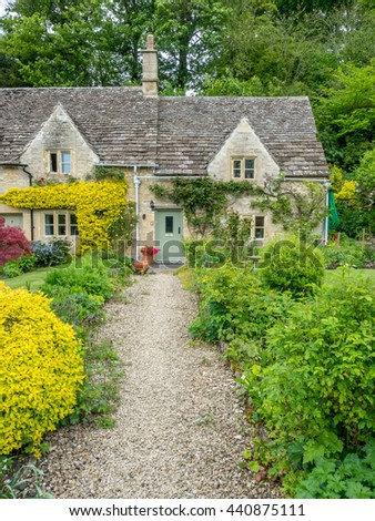 Traditional stone cottages in the peaceful  Cotswold village of Bibury, Bibury, England, under cloudy sky
