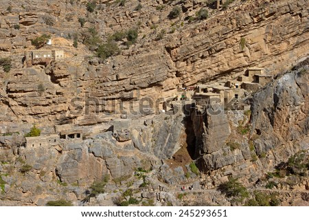 Traditional stone houses in a small cliff hamlet near Sroot in the Jebel Akhdar mountains in the Sultanate of Oman. - stock photo