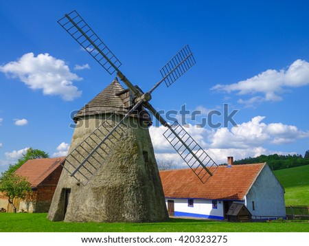 Traditional stone windmill with rotating shingle roof built in 1842. Located near the town of Kuzelov, Czech republic, Europe. - stock photo