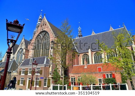 Traditional street lamp and Gothic building of the Oude Kerk (Old Church) in Amsterdam, the Netherlands - stock photo