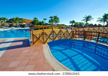 Traditional style bridge over the swimming pool at the luxury caribbean mexican resort.