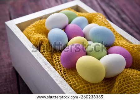 Traditional sugar and chocolate easter eggs in a white wood container on a wood table.  - stock photo