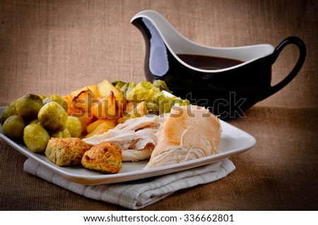 Traditional Sunday dinner with gravy boat. - stock photo