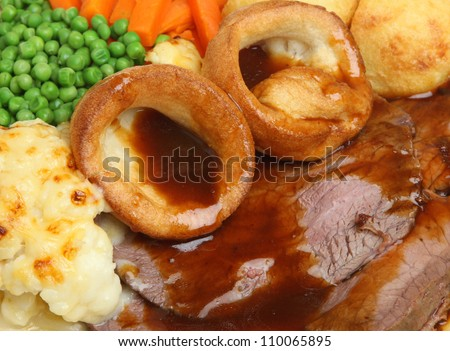 Traditional Sunday roast beef dinner with Yorkshire puddings and gravy. - stock photo