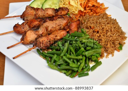 Traditional suriname food, chicken sate with fried rice - stock photo