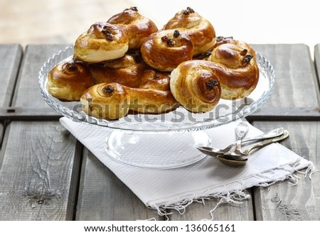 """Traditional swedish buns. A saffron bun, in Swedish lussebulle or lussekatt, Norwegian """"lussekatt"""" is a rich yeast-leavened sweet bun that is flavoured with saffron and cinnamon and contains currants. - stock photo"""