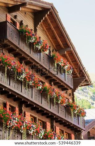 Traditional Swiss chalet with flowers on balconies at Zermatt village of  Switzerland in summer