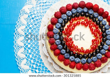 Traditional tasty raspberry and blueberry cheesecake on wooden table - stock photo