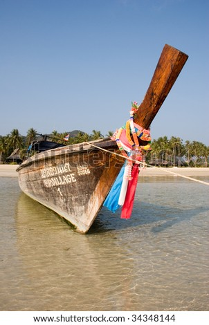 Traditional Thai boat on tropical beach - stock photo