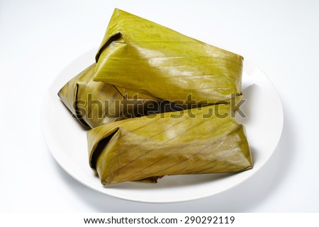 Traditional Thai dessert, Glutinous rice streamed with banana wrap banana leaf. (Khao Tom Mat) isolated on white background - stock photo