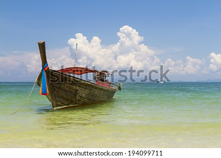 Traditional thai longtail boat landing on sea coast. Krabi, Andaman Sea, Thailand - stock photo